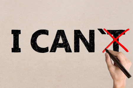 i t: I can, self motivation concept. Businessman crossing out letter T on light surface so that it reads i can