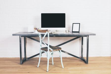 Creative antieke stoel naast designer bureau met een leeg computerscherm en fotolijstjes. Mock up