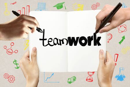 notepads: Teamwork concept with hands holding and writing in notepad together on concrete background with colorful business sketches Stock Photo