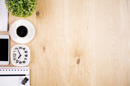 Top view of wooden desktop with clock, stationery items, coffee cup and plant. Mock up