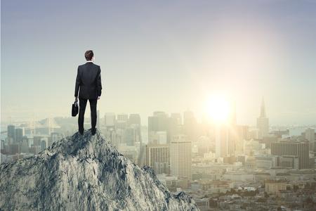 Concept de recherche avec homme d'affaires debout sur le dessus de la montagne et en regardant le soleil couchant sur la ville