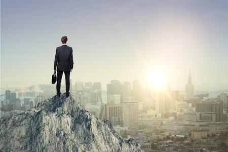 Research concept with businessman standing on mountain top and looking at sun setting over city