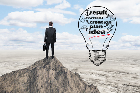 top mountain: Business idea concept with abstract lightbulb sketch and thoughtful businessman on mountain top looking into the distance Stock Photo
