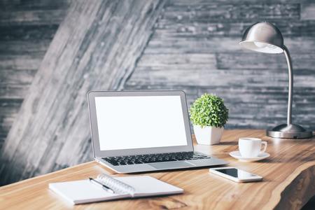 Hölzerner Designer Arbeitsplatz mit leeren weißen Laptop, Schreibwaren, Kaffeetasse, Handy, Pflanze und Tischlampe. Attrappe, Lehrmodell, Simulation
