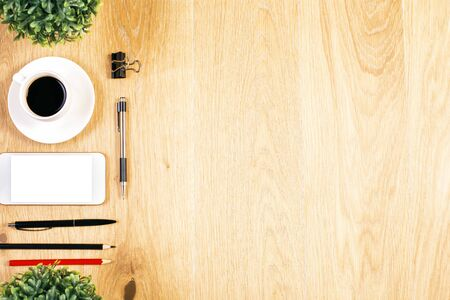 item: Top view of wooden desktop with blank white smart phone, coffee cup, plants and stationery items. Mock up