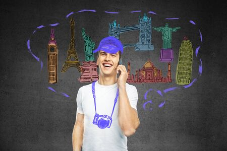 travel phone: Travel concept with camera and cap sketch on young smiling guy having phone conversation on dark concrete background Stock Photo
