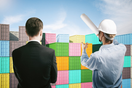 explaining: Dock worker pointing at colorful cargo containers and explaining something to businessperson. 3D Rendering Stock Photo