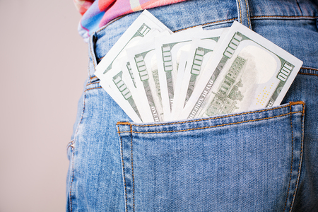 bribery: Bribery and corruption concept with dollar banknotes in jeans back pocket
