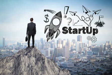 man illustration: Start up concept with rocket ship sketch and businessman looking at city from mountain top Stock Photo
