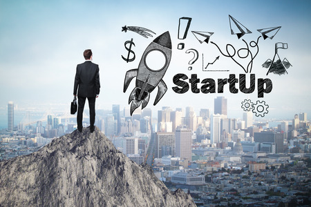 staring: Start up concept with rocket ship sketch and businessman looking at city from mountain top Stock Photo