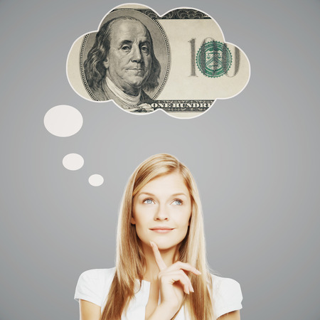 finance girl: Pretty young woman thinking about money on light grey background