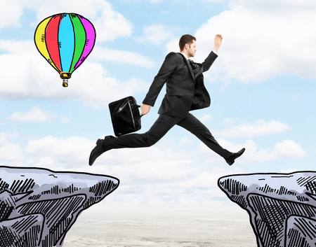 balloon drawing: Success concept with young businessman jumping from cliff to cliff and air balloon drawing on landscape background