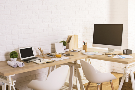 Creative designer workspace with blank laptop and computer screens in interior with wooden floor and white brick wall. Mock up