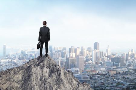 Koncepcja Badania z biznesmen stojący na szczycie góry i patrząc na miasto