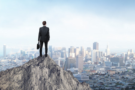 Onderzoek concept met zakenman die zich op de bergtop en op zoek naar de stad Stockfoto