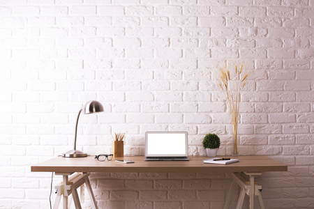 Front view of creative wooden designer desktop with blank white laptop, decorative plants, table lamp, glasses and stationery items on white brick wall background. Mock up