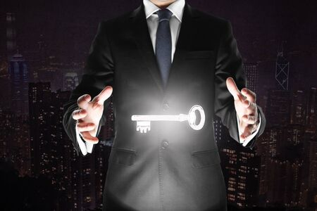 dark city: Businessman holding levitating key on abstract dark city background