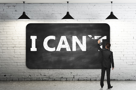 I T: I can, self motivation concept. Businessman wiping letter T off chalkboard in brick room so that it reads i can. 3D Rendering Stock Photo