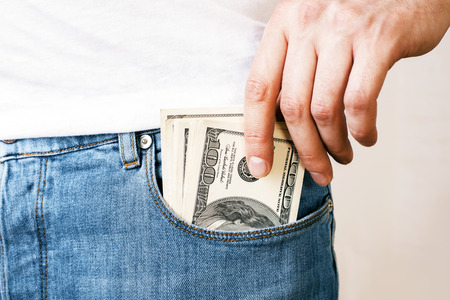 pocket: Bribery and corruption concept with mans hand putting dollar banknotes in jeans pocket
