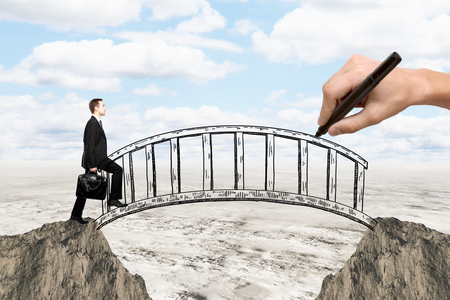 Success concept with hand drawing bridge over gap between two cliffs and businessman walking across it on landscape background