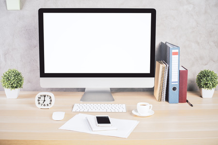 Creative designer desktop with blank white computer monitor, keyboard, coffee cup, clock, smartphone, paperwork, stationery and other items. Mock up Imagens