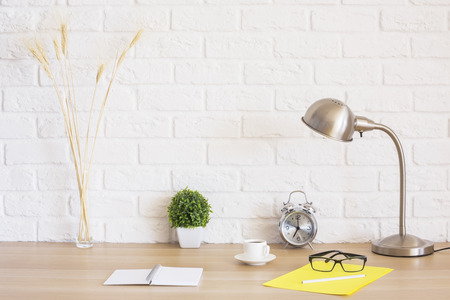 interior designer: Creative desk with glasses, alarm clock, notepad, coffee cup, wheat spikes and other items