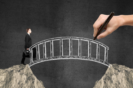 Success concept with hand drawing bridge over gap between two cliffs and businessman walking across it on dark concrete background