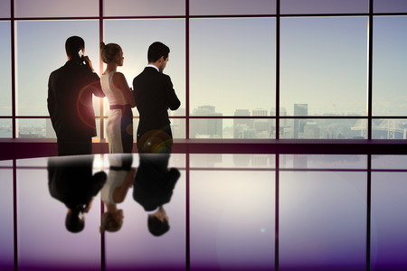 businessman suit: Backlit businesspeople looking out window with city view and sunlight. Concept of teamwork and partnership
