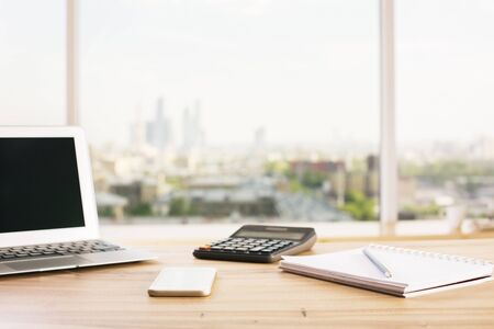 stationery items: Front view of wooden office table with blank laptop, calculator, smartphone and stationery items on blurry city background. Mock up Stock Photo