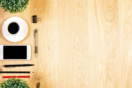 item: Top view of wooden desktop with blank smart phone, coffee cup, plants and stationery items. Mock up Stock Photo