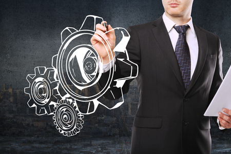 businessman suit: Teamwork concept with young businessman holding document in hand and drawing abstract gear sketch on concrete city background