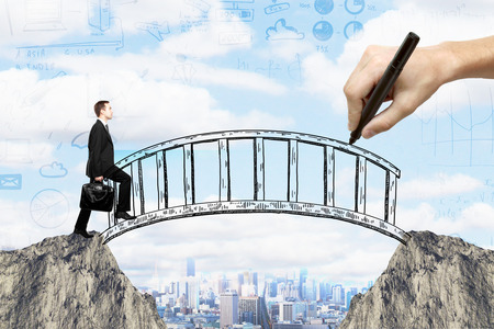 financial cliff: Success concept with hand drawing bridge over gap between two cliffs and businessman walking across it on city background with business sketches