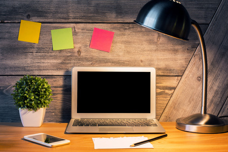 up view: Front view of creative hipster desktop with blank laptop screen, illuminated table lamp, smartphone, plant, colorful stickers and other stationery items. Mock up