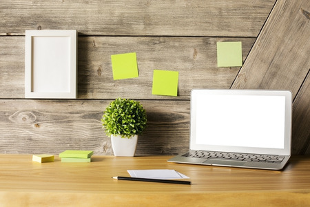 office wall: Closeup of creative wooden designer desktop with blank white laptop screen, picture frame, plant and stationery items. Mock up