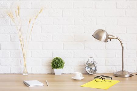 Creatieve desktop met een bril, wekker, kladblok, kopje koffie, tarwe spikes en andere items