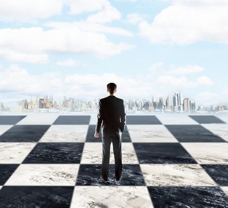 planeación estrategica: concepto de planificación estratégica con el empresario de pie en el tablero de ajedrez y mirando a la ciudad en el fondo de cielo con nubes