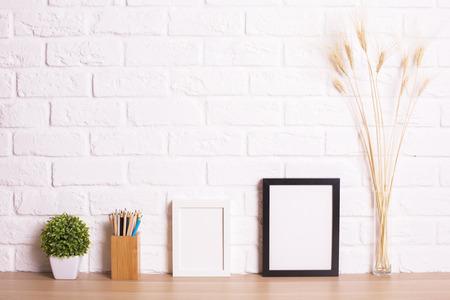 Tavolo in legno con cornici vuote decorative immagine, pianta, spighe di grano e articoli di cancelleria su sfondo bianco muro di mattoni. Modello
