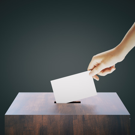 Mano con voto de ballet de colada en blanco en la urna de madera sobre fondo gris oscuro. Concepto de votación. Maqueta, 3D