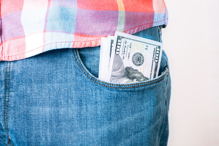 bribery: Bribery and corruption concept with dollar banknotes in jeans pocket