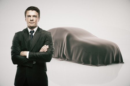 intrigue: Businessman with crossed arms standing in front of car covered with grey veil on light background. Car developer presenting new product Stock Photo