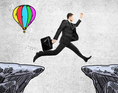 balloon drawing: Success concept with young businessman jumping from cliff to cliff and air balloon drawing on concrete background