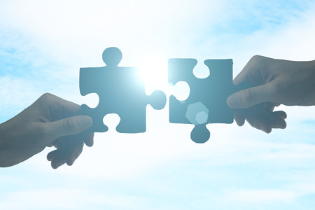 Partnership concept with hands putting puzzle pieces together on sky background with sunlight Stockfoto