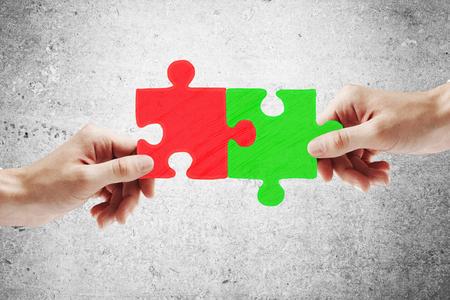 Partnerschaftskonzept mit den Händen, die zusammen grüne und rote Puzzlespielstücke auf konkretem backgroud setzen
