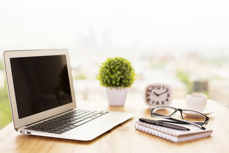 Side view of wooden office desk with blank laptop, plant, clock, glasses, stationery items and coffee cup on blurry background. Mock up Stockfoto