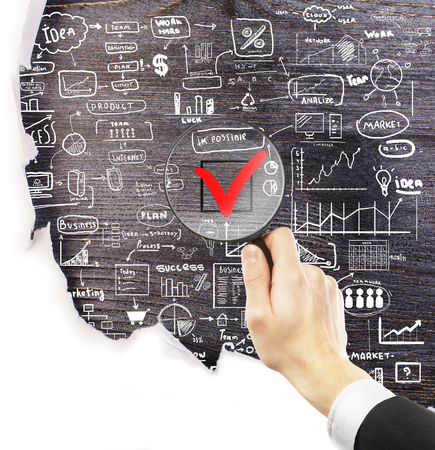 male wood tick: Businessman hand holding magnifier over red checkmark with business drawings around on dark wooden background under torn paper. Nothing is impossible concept