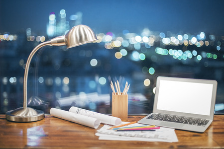 night table: Front view of creative designer desktop with blank white laptop, stationery items and table lamp on blurry night city background. Mock up