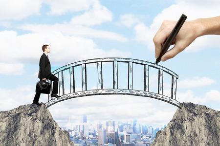 Erfolgskonzept mit der Hand Brücke über Lücke zwischen zwei Klippen zeichnen und Unternehmer über sie auf Stadt Hintergrund zu Fuß Standard-Bild