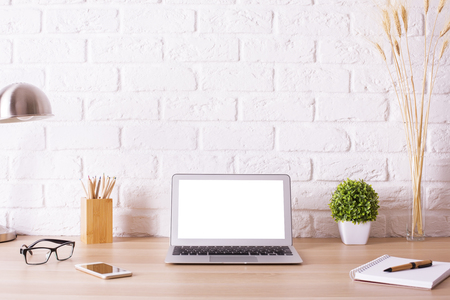 Front view of creative hipster desktop with blank white laptop, smart phone, glasses, lamp, stationery and decorative items on white brick wall background. Mock up