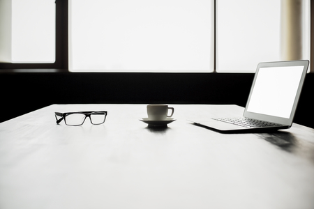 backlit keyboard: Backlit office desktop with blank white laptop screen, coffee cup and glasses. Mock up