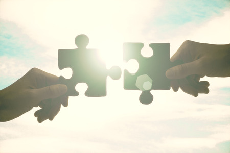 Partnership concept with hands putting jigsaw pieces together on sky background with sunlight Banque d'images